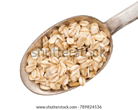 Healthy food option, porridge etc. Coarsely rolled whole grain organic oat flakes. On metal spoon. Isolated on white.