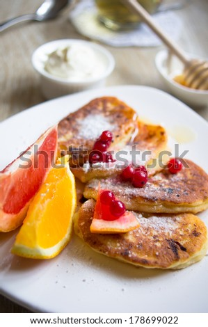 Healthy food, pancakes with fresh fruits, honey and sour cream, green tea