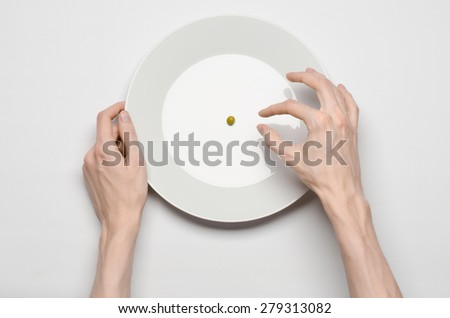 Healthy food theme: hands holding a plate of green peas on a white table top view - stock photo