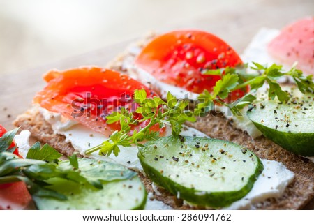 Healthy food theme. Sandwiches made of Finnish rye crisp bread, soft cheese, cucumber, tomato, parsley and black pepper - stock photo