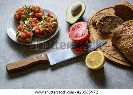 Healthy food. Vegetable appetizers. Sandwich : Rye Bread, Avocado, Tomatoes - stock photo