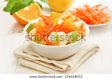 Healthy food. Vegetarian fruit salad with carrots, apples, bananas and orange slices in bowl on white wooden table - stock photo