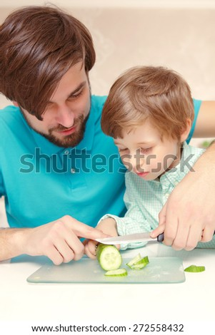 Healthy food. Young father in casual clothes teaching his small son how to cut cucumber