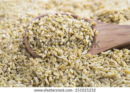 Healthy Freekeh in wooden spoon. - stock photo