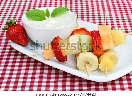 Healthy fresh fruit on kabobs with a side yogurt dip. - stock photo
