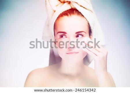 Healthy fresh girl cleaning face with cotton swab