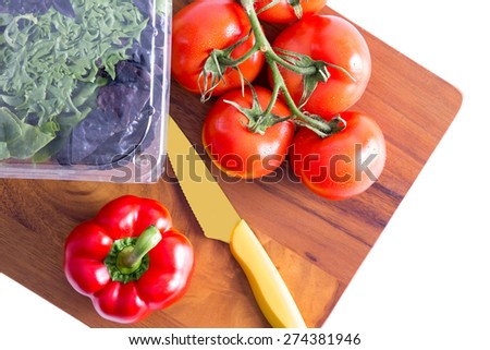 Healthy fresh salad ingredients on a chopping board with a sharp paring knife with three varieties of lettuce in a punnet and vine tomatoes with red bell pepper alongside, isolated on white - stock photo