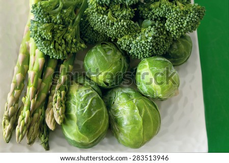Healthy fresh vegetables broccoli, brussels sprout and asparagus bunch on a white plate against green background. - stock photo