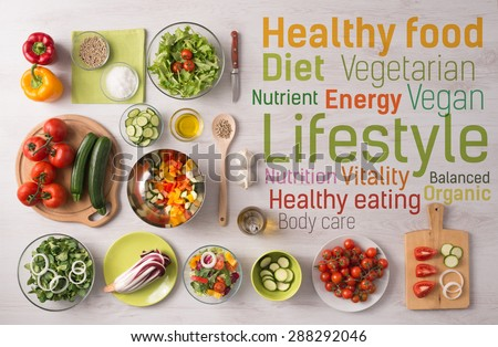 Healthy fresh vegetables salad preparation with kitchen utensils on a table and nutrition text concepts - stock photo