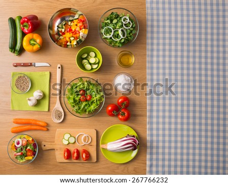 Healthy fresh vegetarian food on kitchen table with checked tablecloth on the right, top view - stock photo