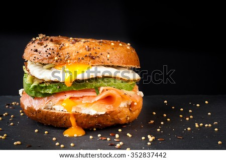 Healthy freshly baked bagel filled with smoked salmon lox and topped with avocado and an egg. Served on a gray slate table against a dark background.