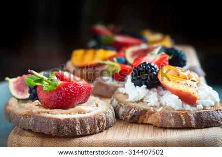 Healthy fruit topped open sandwich of Wholemeal rye bread with strawberry, blackberry, grilled peach and fig. Served on a wooden board. - stock photo
