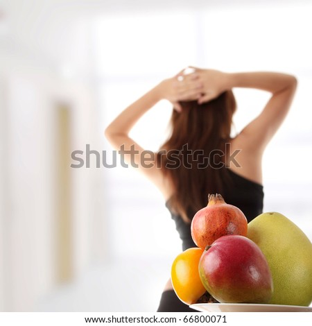 Healthy fruits with fitness girl in background - stock photo