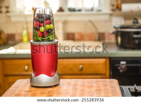 Healthy fruits with small blender on a cutting board getting ready for making a smoothie in a kitchen setting. - stock photo
