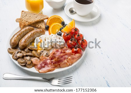 Healthy Full English Breakfast -  plate with poached eggs, sausages,  mushrooms, toasts and bacon, fruit, cup of fresh coffee and orange juice on white background - stock photo