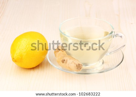 Healthy ginger tea with lemon on wooden background
