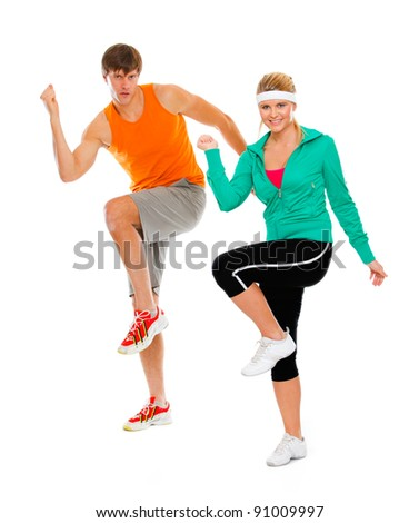 Healthy girl and guy in sportswear doing aerobics isolated on white - stock photo