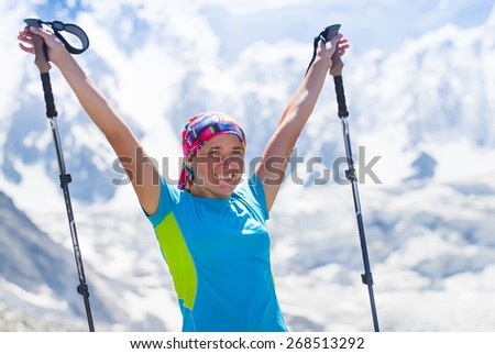 Healthy girl hiker with trekking poles to overcome difficulties in the mountains. Background of high mountains, glaciers in the Himalayas - stock photo