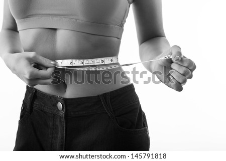 healthy girl measuring herself with a tape measure around her waist