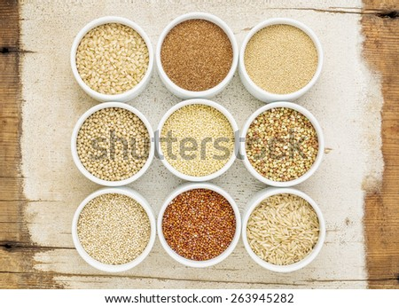 healthy, gluten free grains abstract (quinoa, brown rice, millet, amaranth, teff, buckwheat, sorghum), top view of small round bowls against rustic barn wood - stock photo