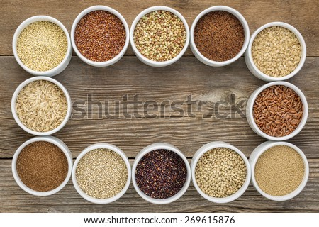 healthy, gluten free grains collection (quinoa, brown rice, millet, amaranth, teff, buckwheat, sorghum) , top view of small round bowls against rustic wood with a copy space - stock photo