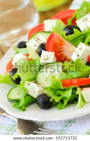 Healthy Greek salad with lettuce, tomatoes, cucumbers, black olives and traditional feta cheese served on a plate - stock photo