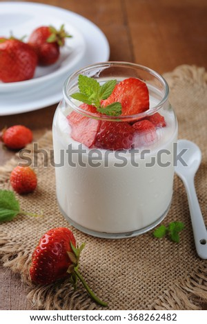 Healthy greek yogurt and fresh strawberries on wooden table - stock photo