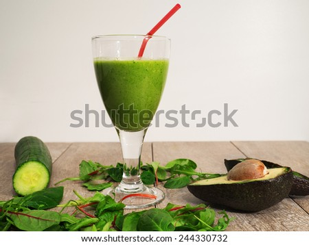 Healthy green fresh vegetable juice smoothie with red straw - stock photo
