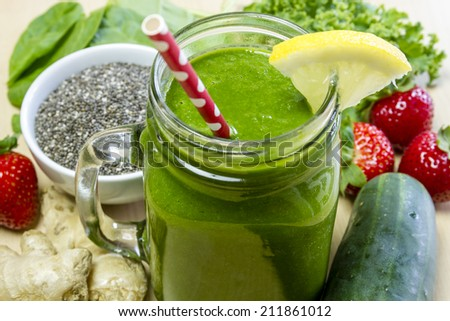Healthy green juice smoothie surrounded by whole fruits, vegetables and chia seeds with lemon garnish and red polka dot straw - stock photo