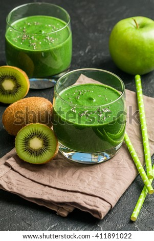 Healthy green smoothie made from  kiwi, bananas and apples in a glass with straws on black table. - stock photo