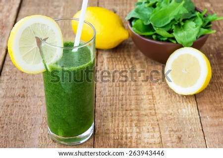 Healthy green smoothie with spinach and lemon on wooden background - stock photo