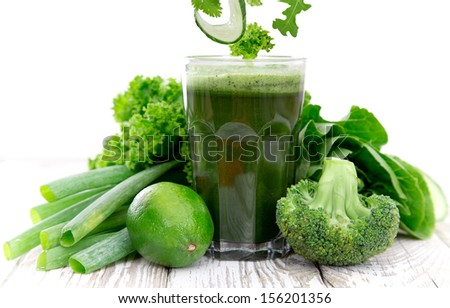 Healthy green vegetable juice on wooden table - stock photo