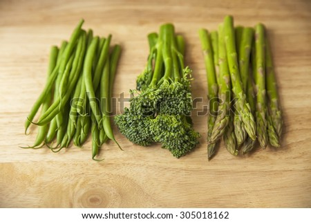 healthy green vegetables on wooden chopping board - stock photo
