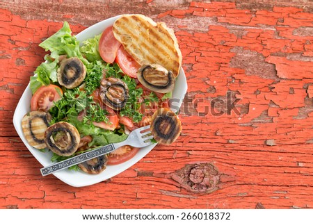 Healthy grilled mushroom salad with tomatoes lettuce parsley served on rustic table with a grilled bread and a fork. Viewed from above - stock photo