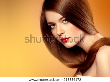 Healthy hair and skin care. Close-up portrait of young pretty girl with professional hairstyle posing in studio. - stock photo