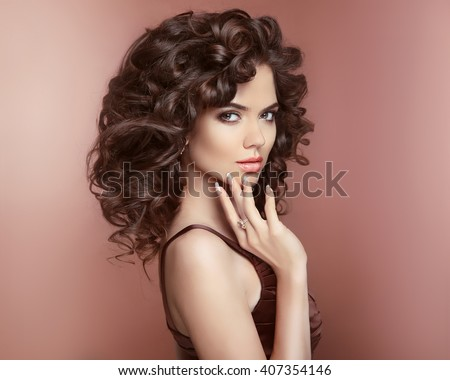 Healthy hair. Beautiful young smiling woman with long curly hairstyle. Manicured nails. Brunette with professional makeup. Elegant lady studio portrait.  - stock photo