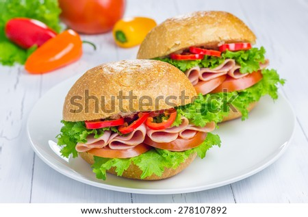 Healthy ham sandwiches on the plate with vegetables on background - stock photo