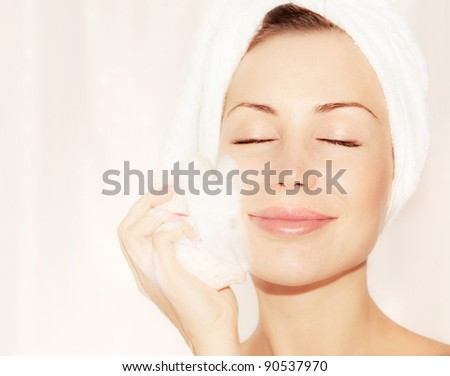 Healthy happy girl taking bath, beautiful young female cleaning face skin,  portrait over soft light background, hygiene and day spa - stock photo