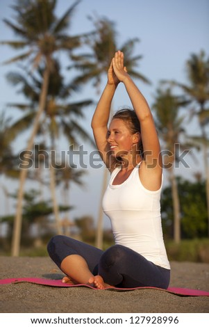 Healthy happy woman doing yoga on mat - stock photo