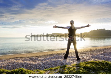 Healthy happy woman enjoying a sunny morning on the beach - stock photo