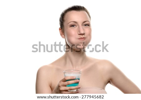 Healthy happy woman rinsing and gargling while using mouthwash from a glass, during daily oral hygiene routine, portrait with bare shoulders, with copy space, isolated on white - stock photo