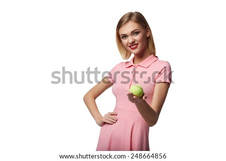 Healthy happy young woman poses while holding tennis ball, on white background - stock photo