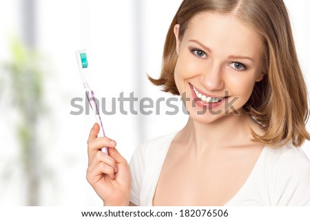 Healthy happy young woman with snow-white smile brushing her teeth with a toothbrush - stock photo