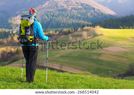 Healthy hiker girl in nature hike. Beautiful young woman hiking happy with Trekking pole stands on a meadow. Background beautiful mountayns and blue sky with clouds - stock photo