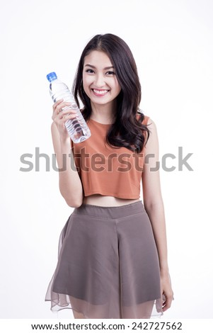 Healthy hispanic latin woman with gym towel drinking out of water bottle