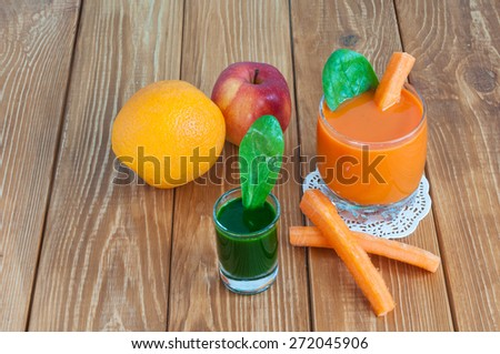Healthy homemade carrot juice in glass and fresh carrot, spinach on light wooden background. Weight loss, healthy food, diet and detoxification - stock photo
