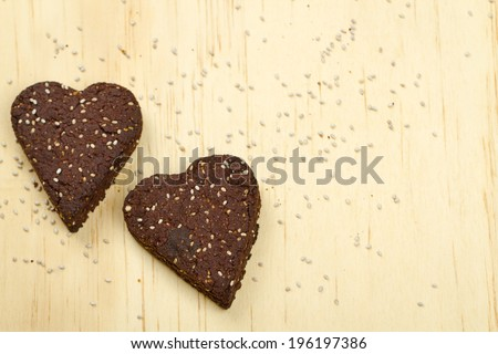 Healthy homemade dark chocolate chia seed love heart cookies on a wooden background - stock photo