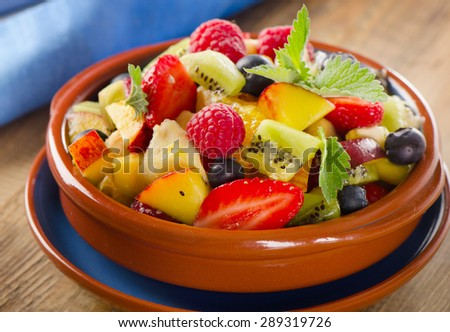 Healthy homemade fruit salad on a  wooden background. Selective focus - stock photo
