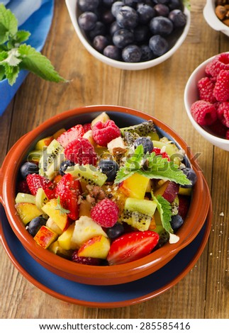 Healthy homemade fruit salad on   rustic wooden background. Selective focus