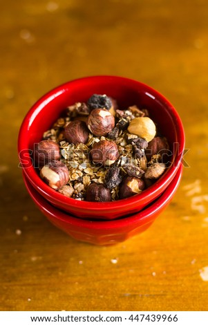 Healthy homemade granola or muesli with hazelnuts in a bowl, selective focus - stock photo